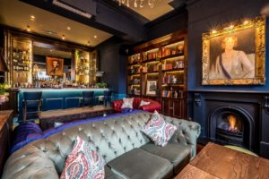 function room with plush sofa, private bar, bookcase and framed painting on the wall