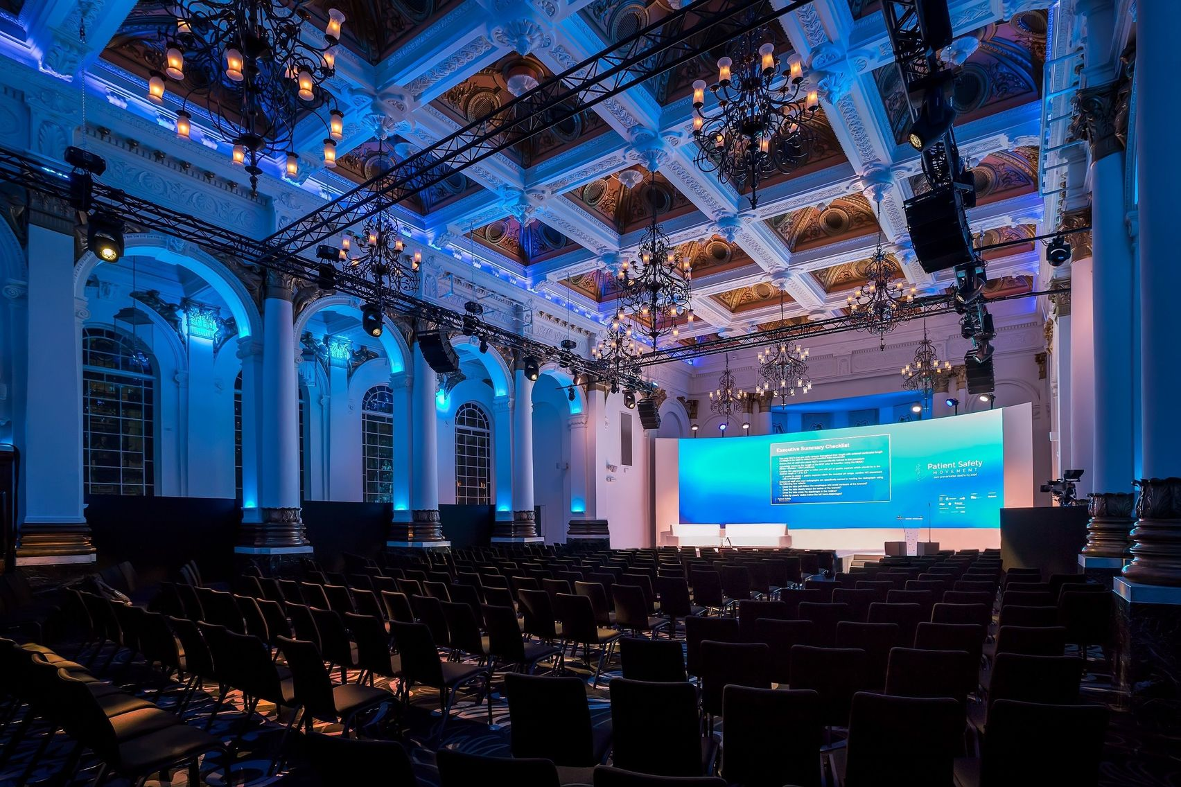 A large london conference venue with high ceilings and arched windows.