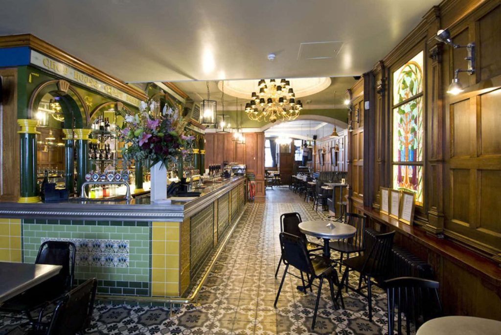 a pub with tiled floors, hanging chandelier, wooden walls and flowers on the bar