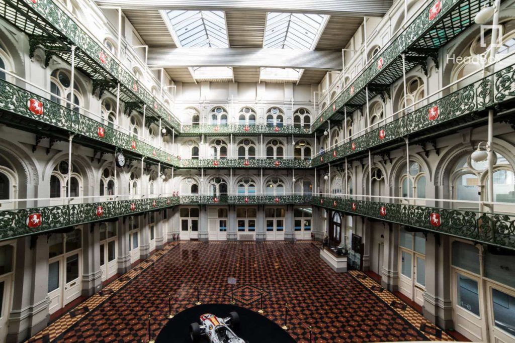 A large atrium which has tiled brown floors and huge skylights running the length of the room
