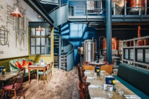 Brewery with tables and chairs and a spiral staircase
