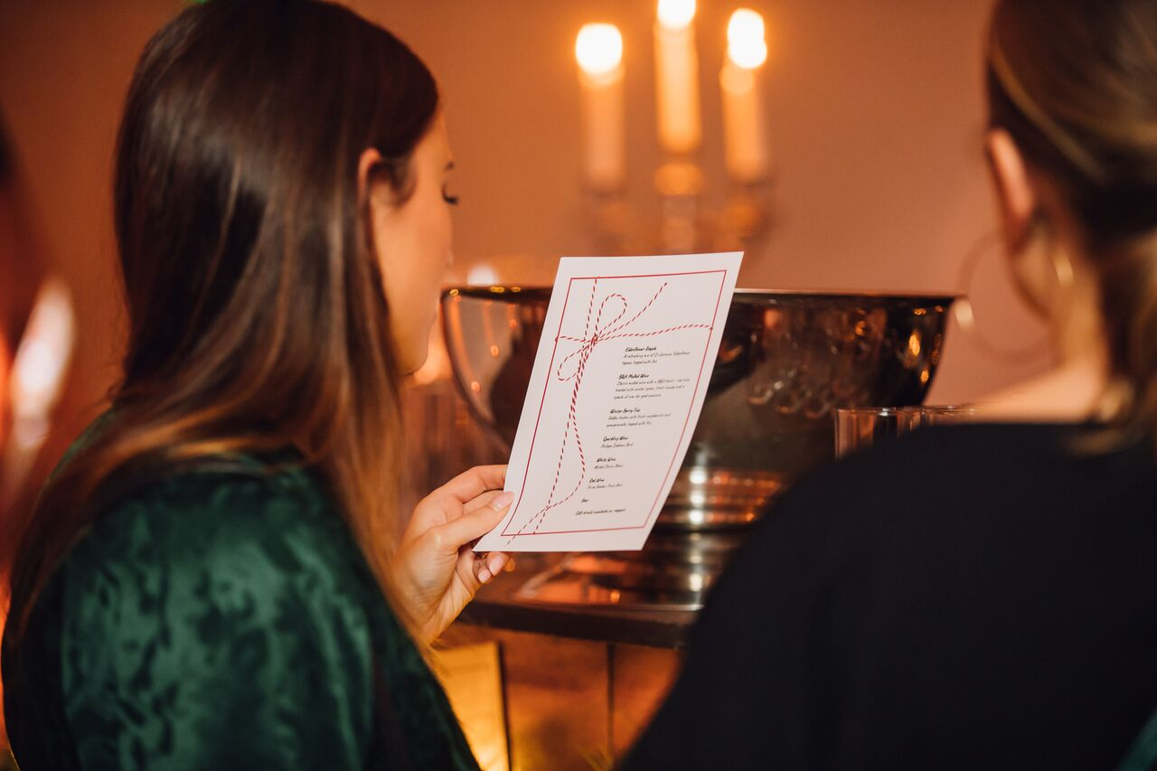 Woman looking at the menu for a Bourne & Hollingsworth event