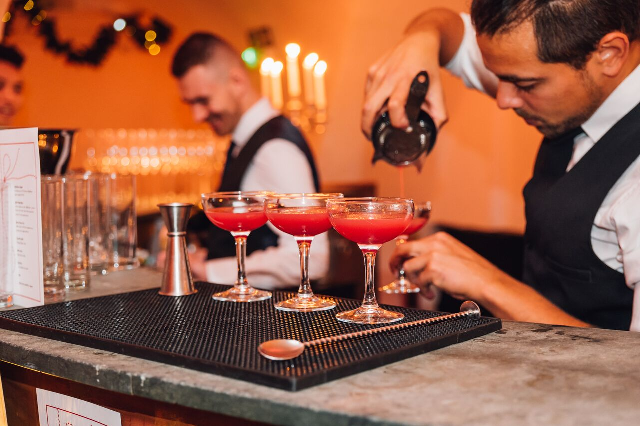 Bartenders mixing and pouring cocktails at Bourne & Hollingsworth's Christmas pop up