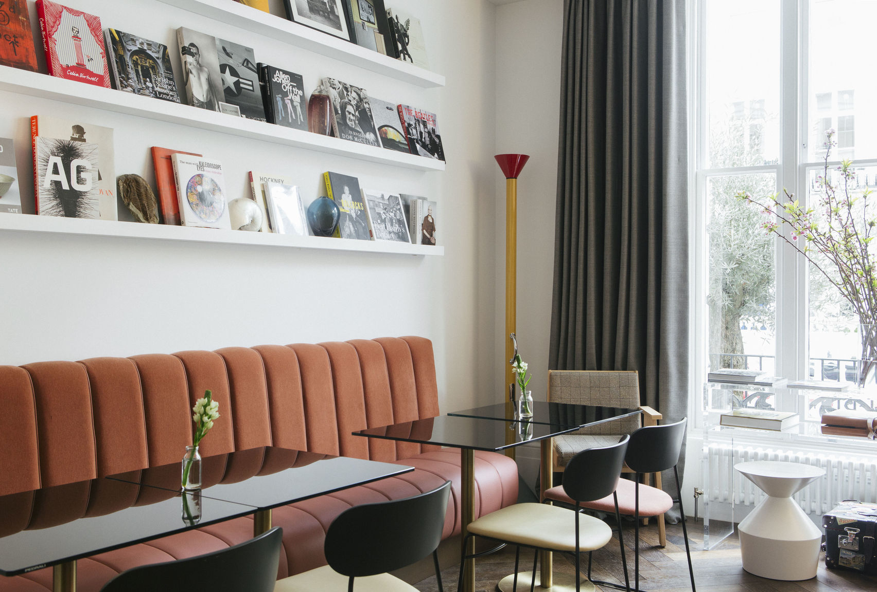 A meeting room with a pink sofa and magazines on shelves. A great option for hotels with meeting rooms hire.