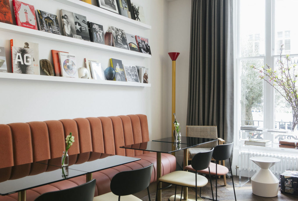 A contemporary venue with a pink velvet sofa and shelves of magazines on the wall.