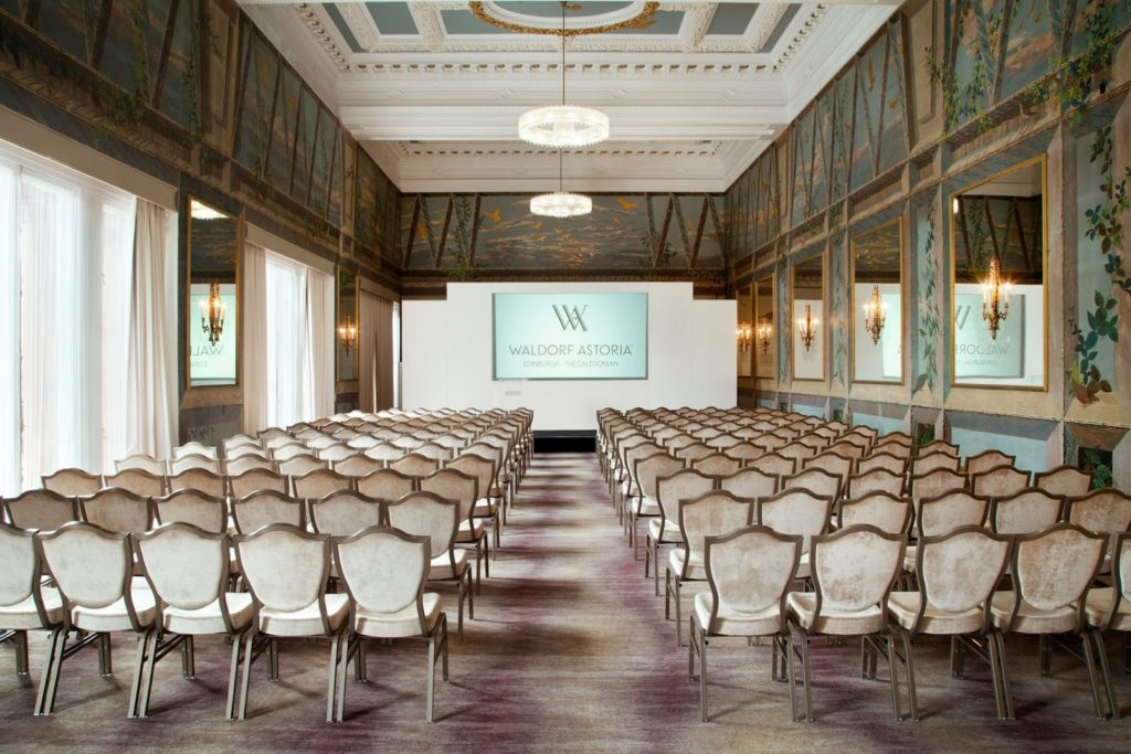 A large Edinburgh conference venue with ornate decoration and rows of white chairs
