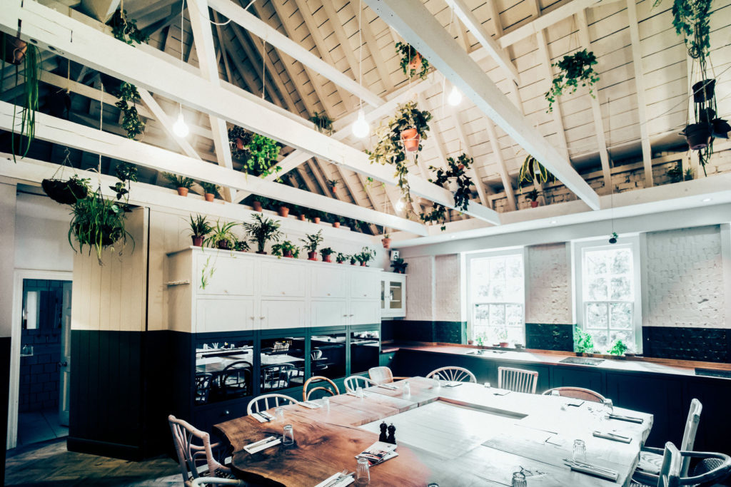 A large white meeting room with u-shaped table in the middle. The space has high ceilings and white beams which are draped with plants and greenery.