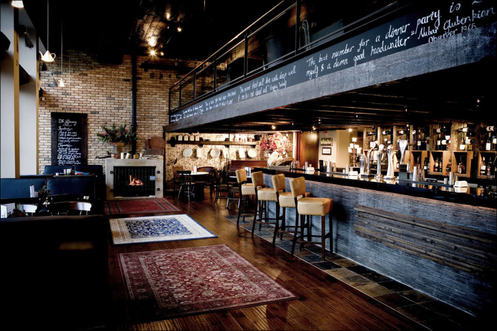 A pub in Edinburgh which has a large dark wooden bar and mezzanine level. A rustic venue with an open fire and exposed brick.