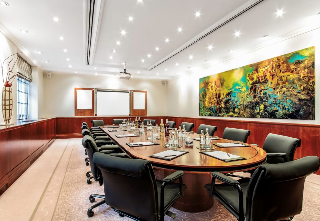 A large colourful boardroom in London. With red paneling around the room and a large colourful painting on the back wall