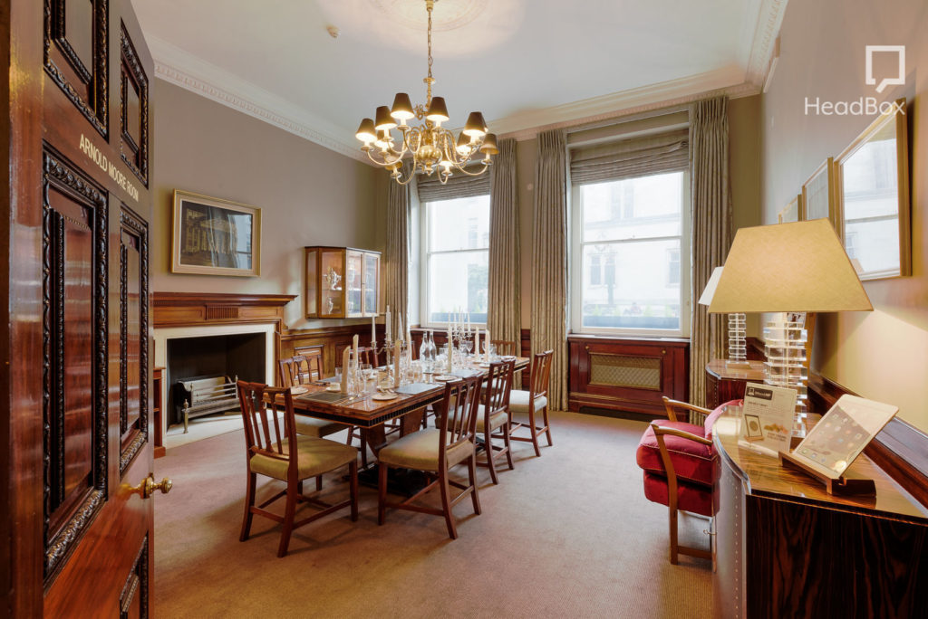 A bright breakfast meeting venues in London with a table in the middle and two large windows on the far wall.