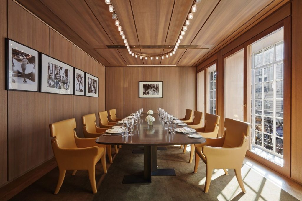 meeting room with wood panelled walls and large floor to ceiling windows allowing lots of natural light