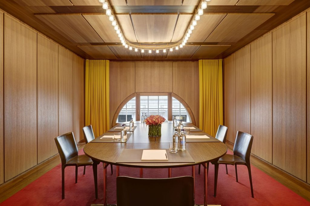 A meeting rom in London with dark wooden paneling and a large wood table in the middle of the room.