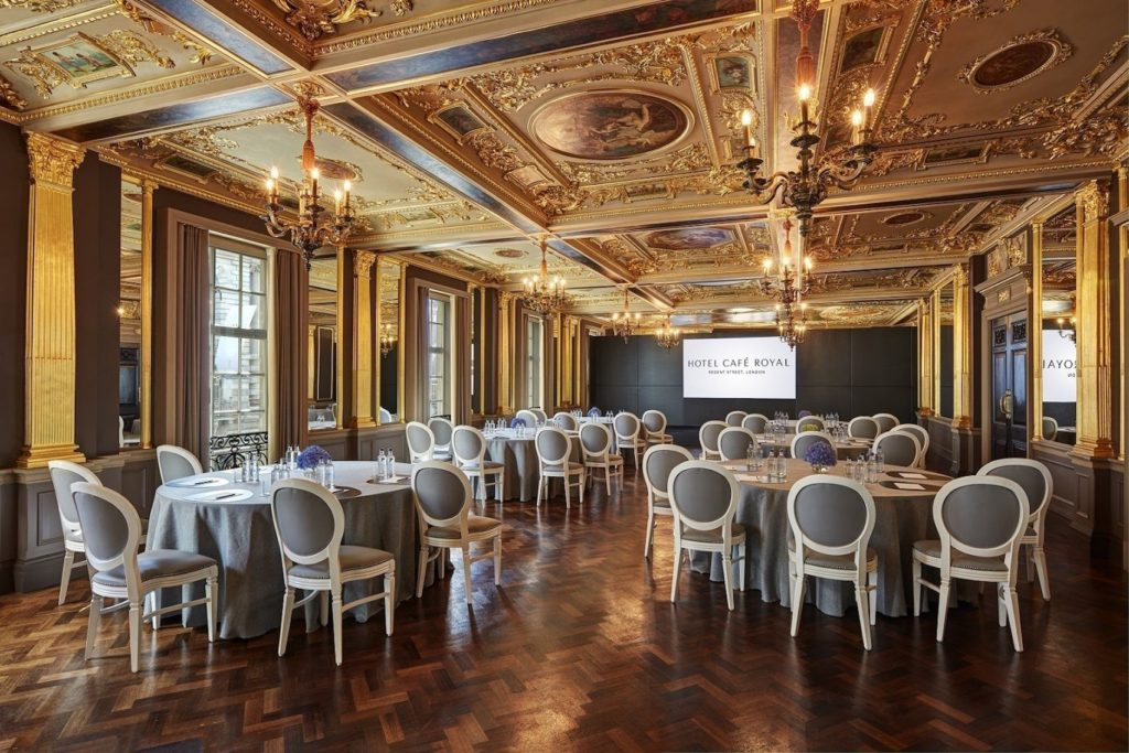 large ballroom with ornate gold detailing on the ceiling set up for a presentation or conference