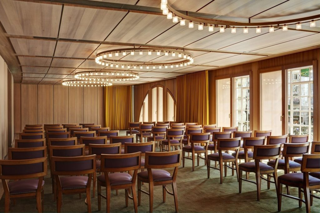 A meeting room with wooden panels in the walls and large circular spotlights
