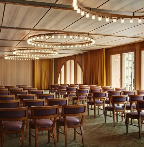 A London conference room with wooden panels on the walls and large circular lighting
