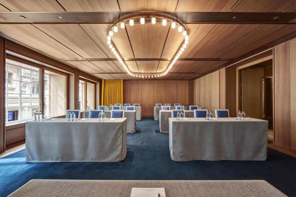 conference room with wood panelling large windows and bright overhead lights