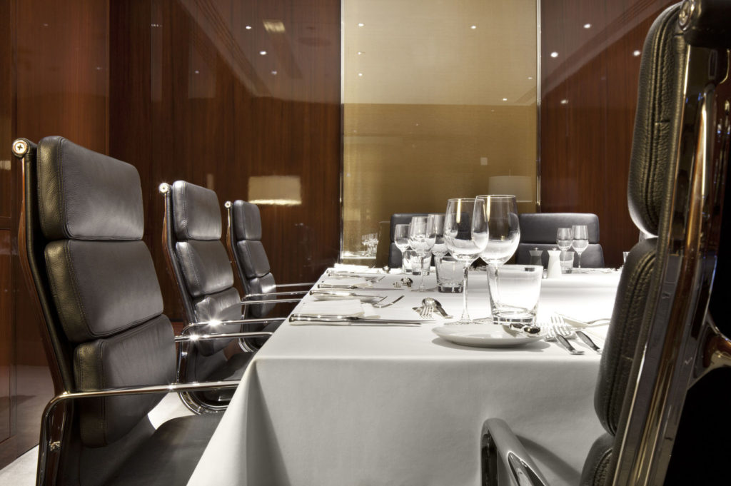 A close up of a meeting room table. A white table cloth is over the table and it is set with cutlery and glasses. Large black office chairs surround it.