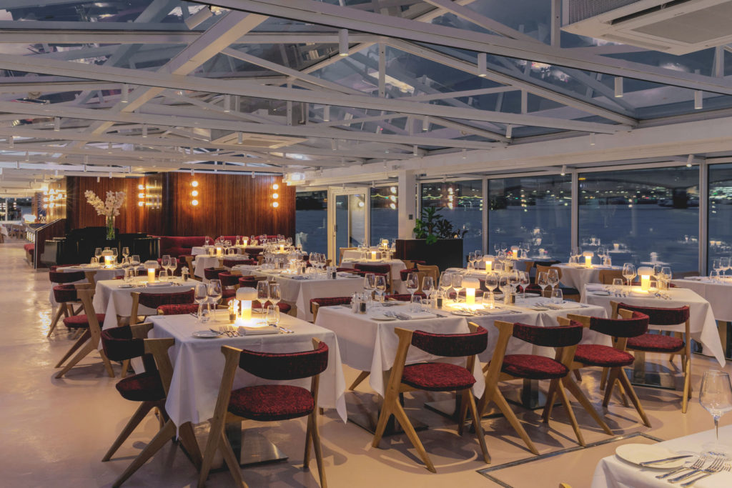 A restaurant on a boat that has a glass ceiling and class walls