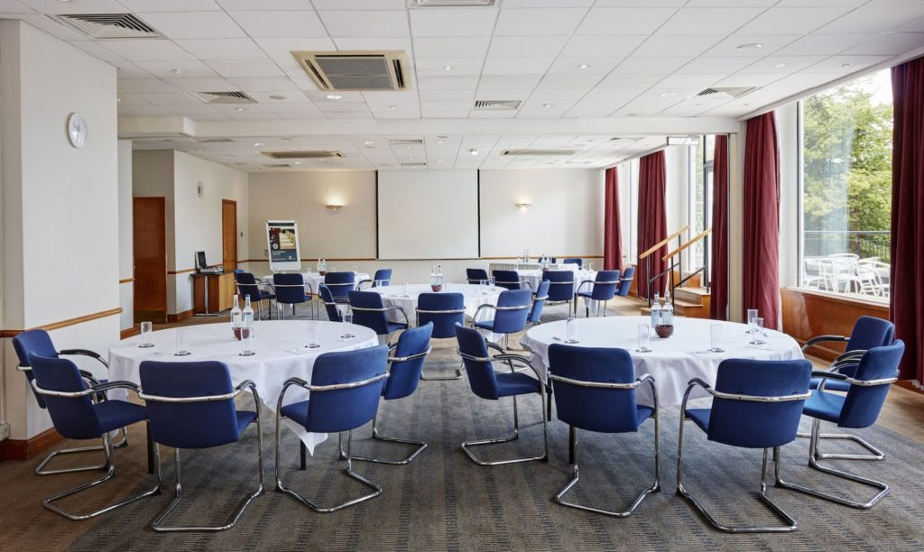 A small conference room with 5 round tables surrounded by blue chairs
