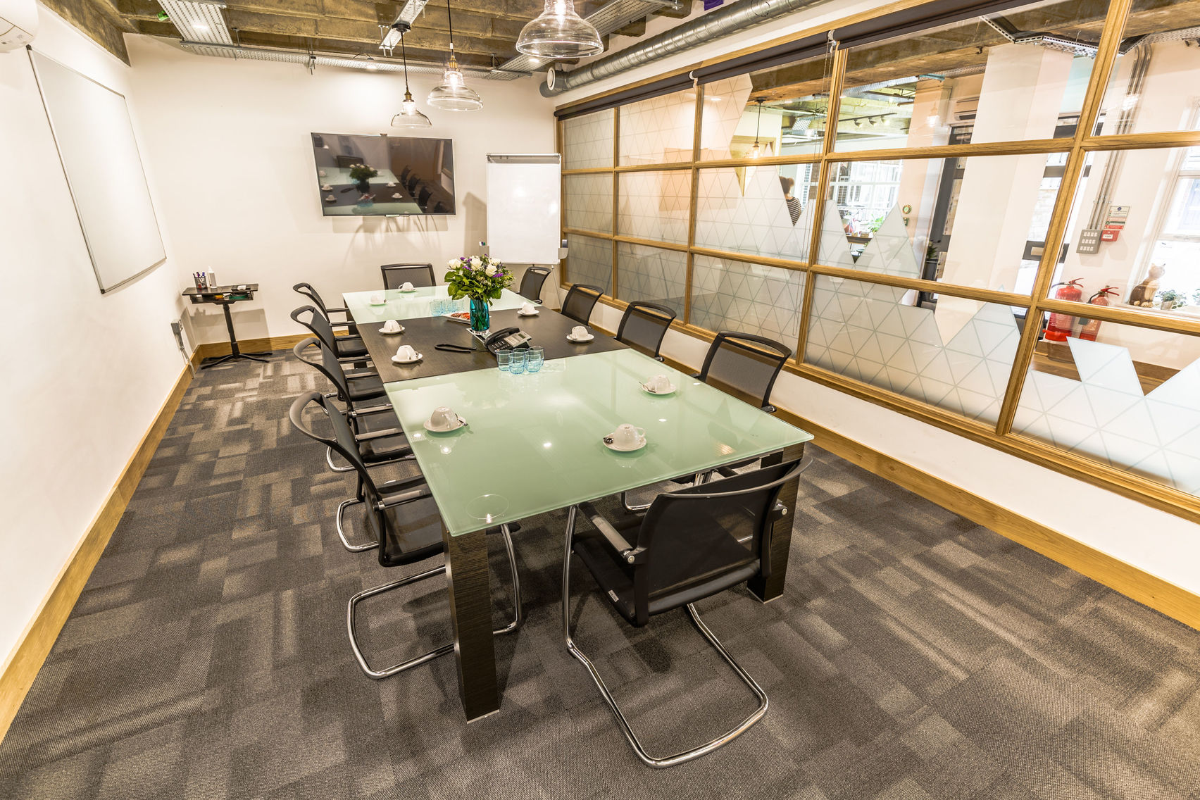 A large meeting room in London with grey carpet and a green and black table and chairs.