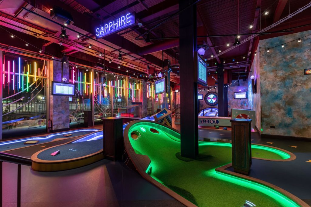 Puttshack is an interactive mini-golf bar. A large green mini-golf station
