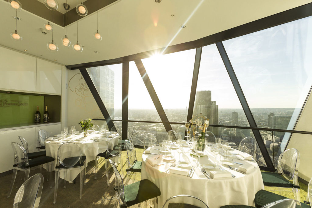 A large dining room in the Gherkin with two circular tables and a large window