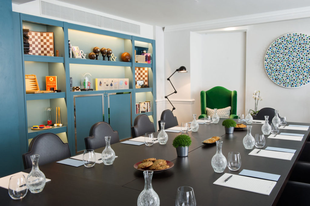 A London meeting room in a hotel with a blue bookcase and black table and chairs