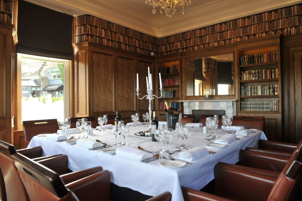 A traditional meeting in Edinburgh. A square table in the middle of the room is draped with a white tablecloth. There is dark wood panelling on the walls and bookshelves.