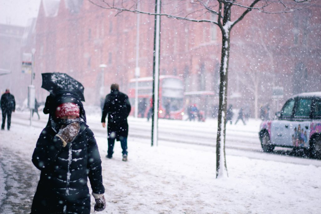 woman walking along the street in London in heavy snow