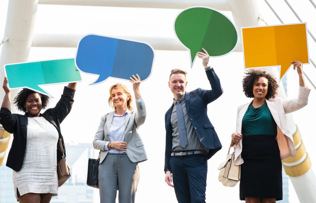 four people holding up speech bubbles