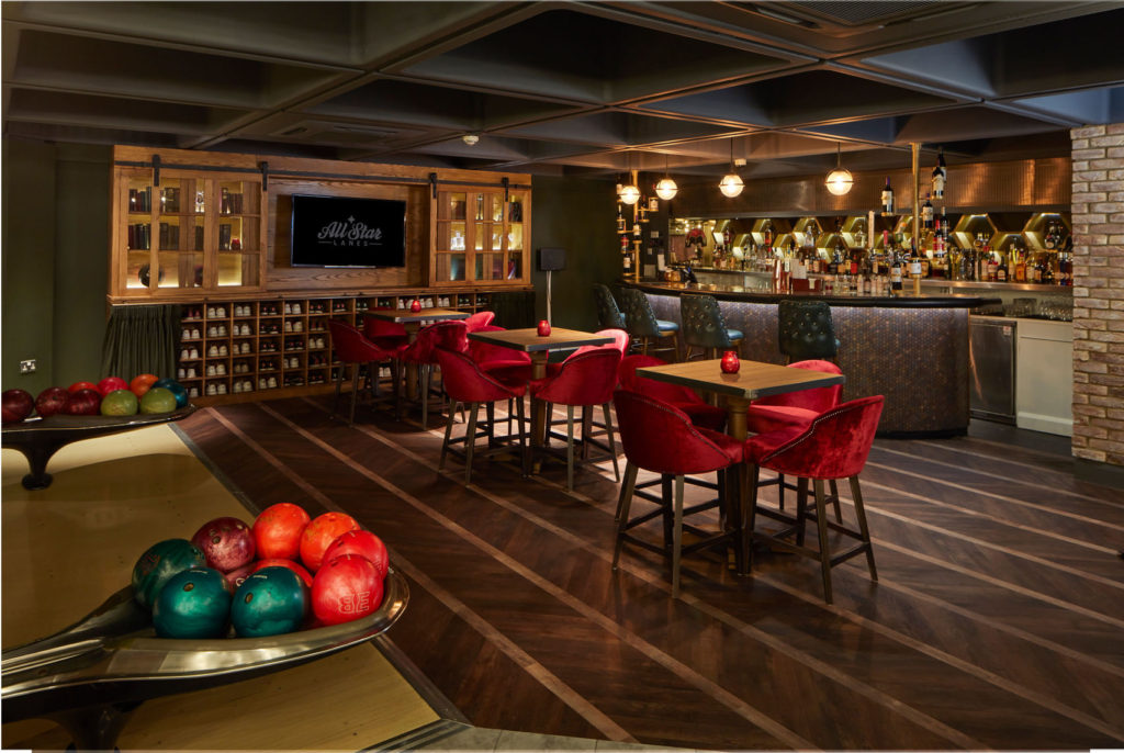 Bar area with three tables with four chairs set around each next to two sets of bowling balls