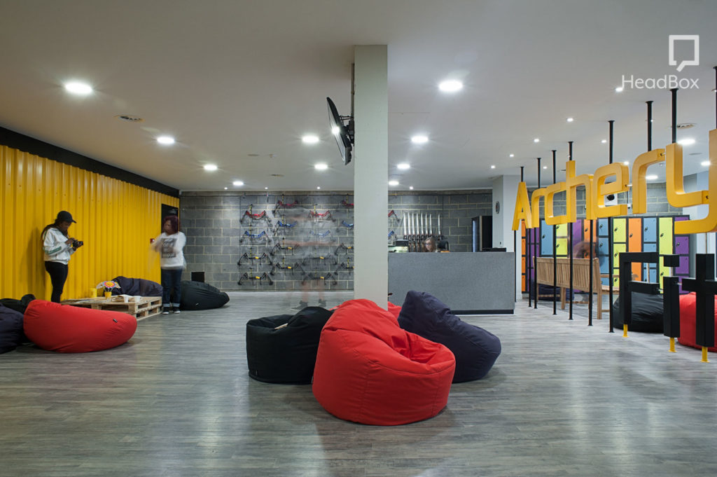 Wide space with black and red bean bag chairs and a set of archery bows on the back wall