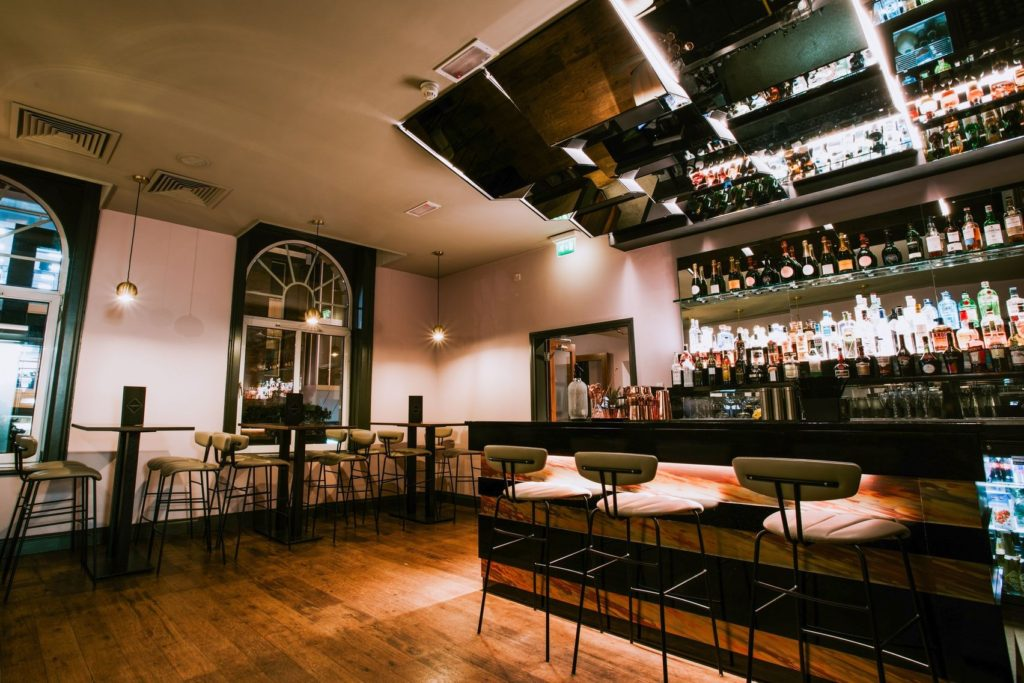 A expansive wooden bar area with stools at tables and the bar, subtle lighting and a wide selection of drinks