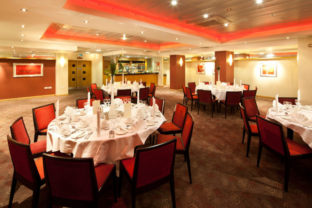 Round tables with tableware within a carpeted dining area with a small bar in the far corner