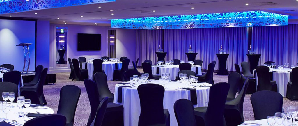 Round table event venue Edinburgh with blue lighting facing a stage area with plinth