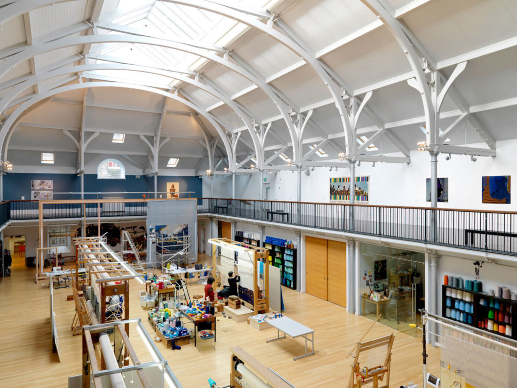 Arched roof over a wide event venue Edinburgh with people working on arts and crafts in the centre of the hall