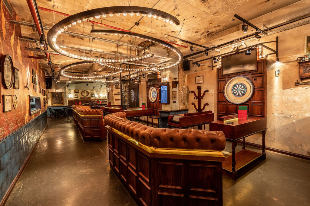 Dartboards surrounded by leather seating in a long event Space with yellow lighting