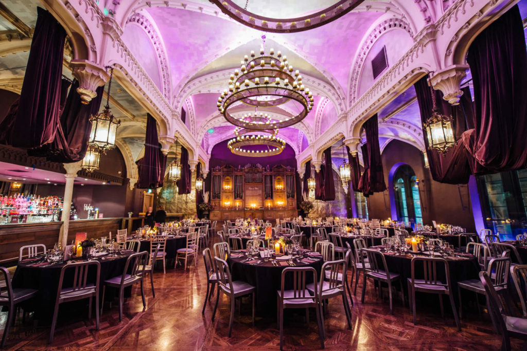 Grand event venue Edinburgh with roundtables and pink lighting next to a bar area