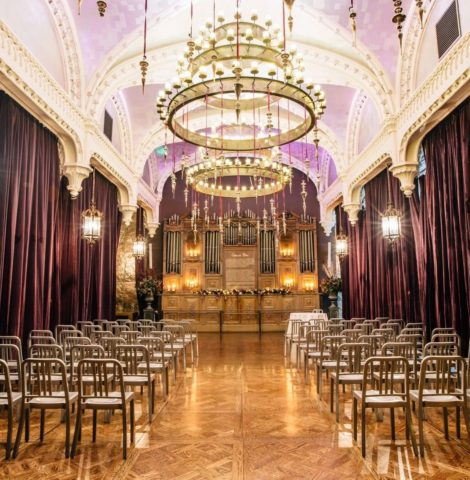 A grand event venue in Edinburgh, high arched ceilings and draped burgundy curtains.
