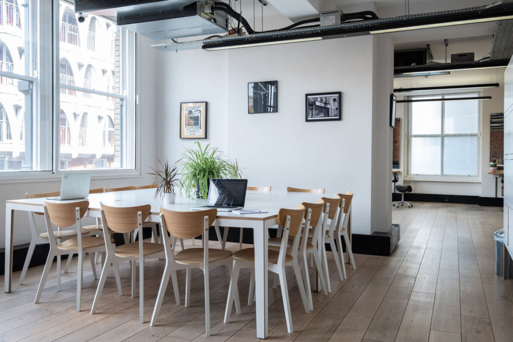 Meeting space with white table and 14 chairs set around it with plants on the table