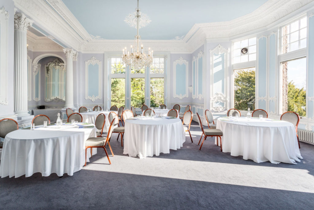 Large spacious private dining room with natural light and chairs at roundtables