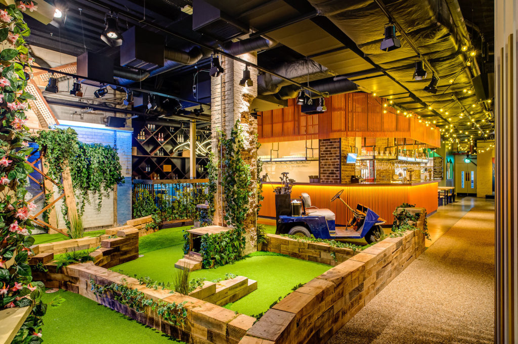 Indoor crazy golf course with bar area lit by bright yellow lighting