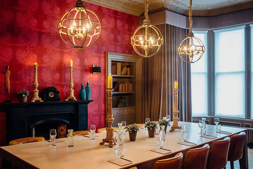 Private dining room in Edinburgh with three hanging lights over a table which is situated in front of a fireplace and bookshelf