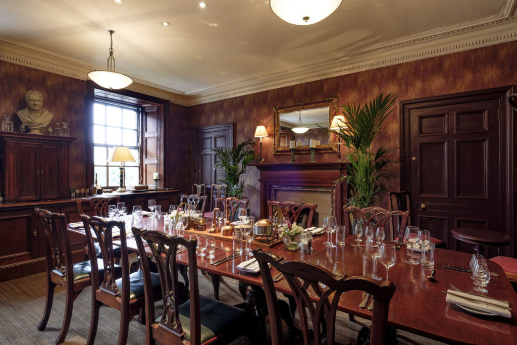 Ornate private dining room in Edinburgh with wine glasses on the table and a fireplace below a mirror