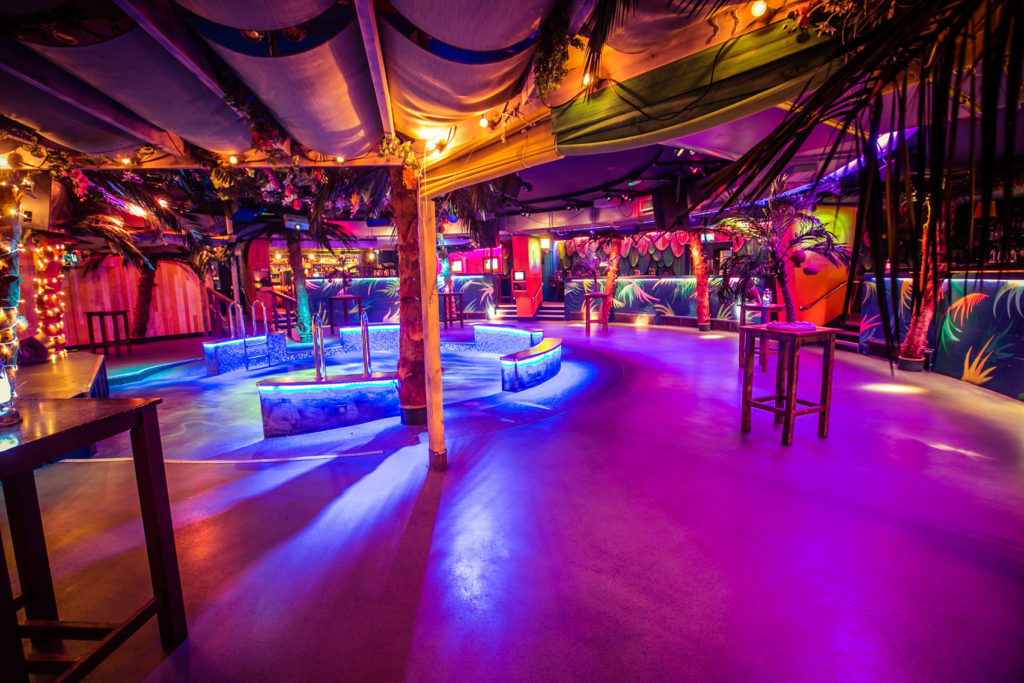 Dance floor with colourful lighting and beach-style bar with raised stage to the left