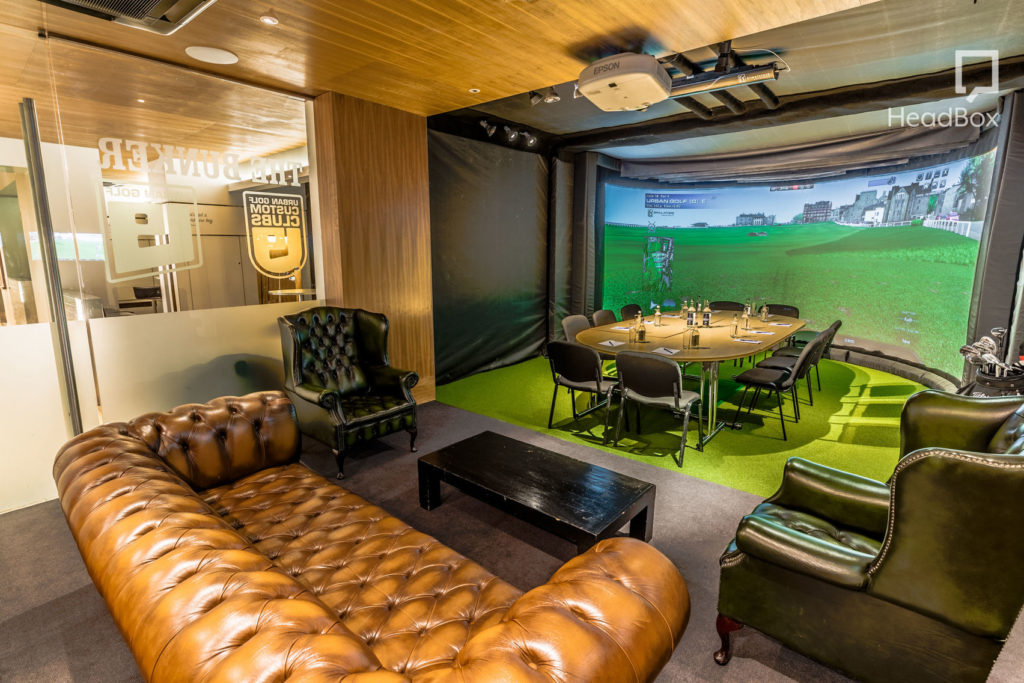 Meeting space with a golf simulator, leather sofa and meeting table with 10 chairs set around it