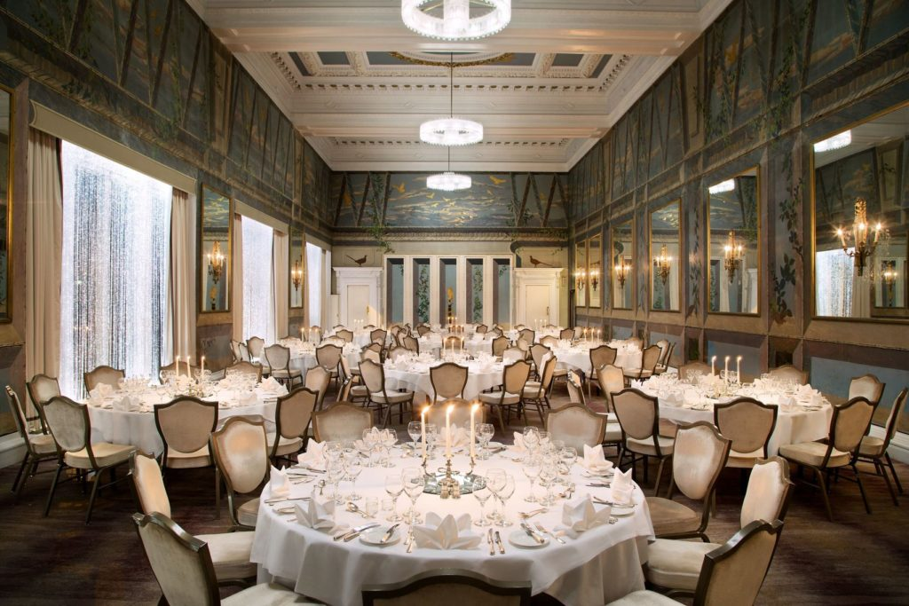 Ornate event venue Edinburgh with round, candle lit tables and mirrored walls