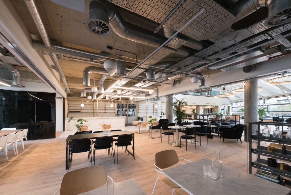 A range of tables and chairs within an expansive Space and bar area at Camden House, London