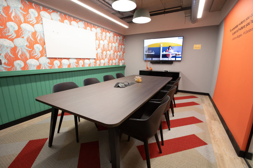 private meeting rooms with orange and green coloured walls and a long brown table facing a TV screen