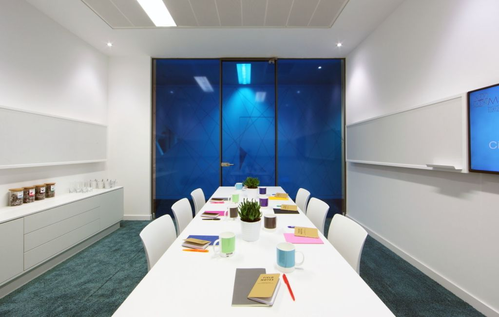 White meeting room with blue glass doors and a TV screen with colourful notebooks on a long white table